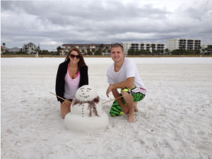 """Brittney Backer (23) and Cody Cheatham (23) of Bloomington, IN., posing with their snowman on Siesta Beach.  An hour of concentrated effort by these two recent college graduates, brought their snowman to life. """"It's my first visit to Siesta Beach and I absolutely love the soft white sand,"""" Brittney said."""