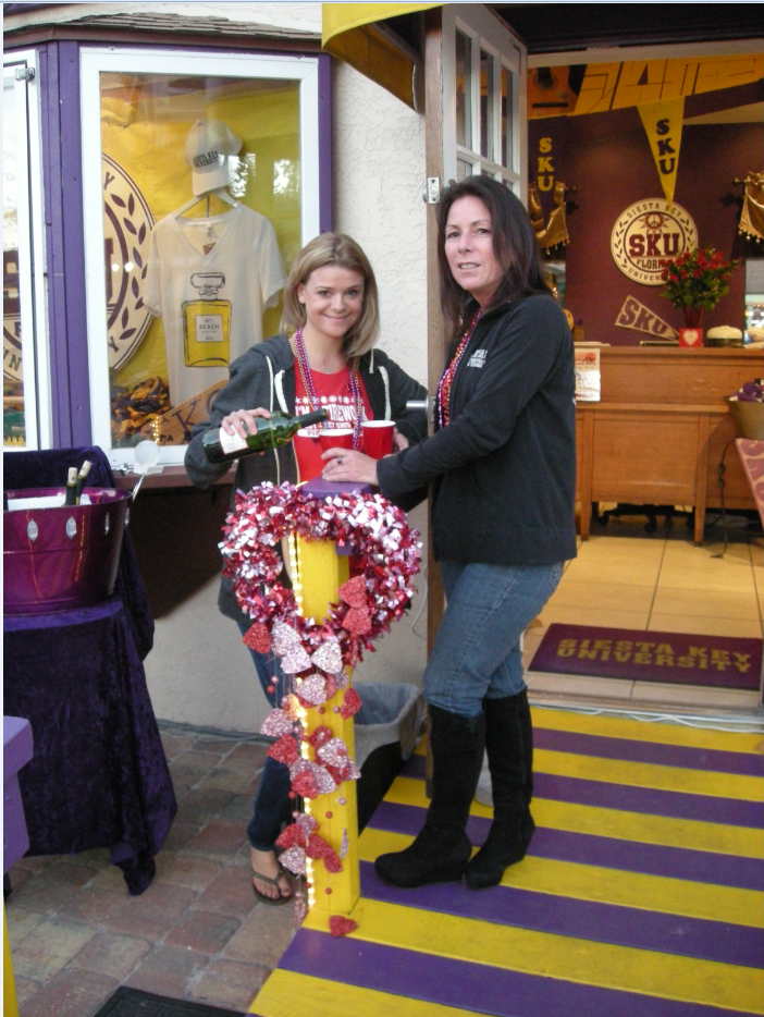 """VALENTINE STROLL Kayla Vail pouring """"Siesta Key University"""" shop owner Lori Dean a sample of Chardonnay during the annual Valentine Stroll in the village on Siesta Key. Lori provided patrons with a complementary taste of Merlot or Chardonnay and chocolate kisses. This was her first year to participate as she just purchased the business a few weeks ago. Lori moved here in 1982 and also owns an airplane maintenance and repair shop at Sarasota airport."""