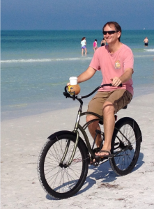 """TIRES ON THE SAND    Siesta Key resident, Pat Bossman peddling along the Siesta Beach shoreline savoring the gulf breeze and the lightly salted air on one of his weekly routines. He, his wife and two daughters moved here from Alexandria, VA three years ago.    Initially concerned about the Florida school system Pat related, """"Phillippi Shores Elementary has been wonderful and our two daughters are thriving.""""    """"Siesta Key is a small town within a small city. I love frequenting businesses where you you get to know people, while also meeting visitors who are seeing Siesta for the first time. We love it here."""" photo by Trebor Britt"""