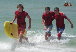 Tanner Weiss racing to the beach with his rescue board while Nick Miller (R) assists simulated victim Jack Perry during a rescue board training exercise.