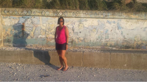 Gina Belz stands in front of the popular wall many have to touch to complete their Siesta beach walk. A frequent traveler, Gina said this is the softest sand she has ever stepped on and will be back again in November. Photo by Donnarose Melvin.