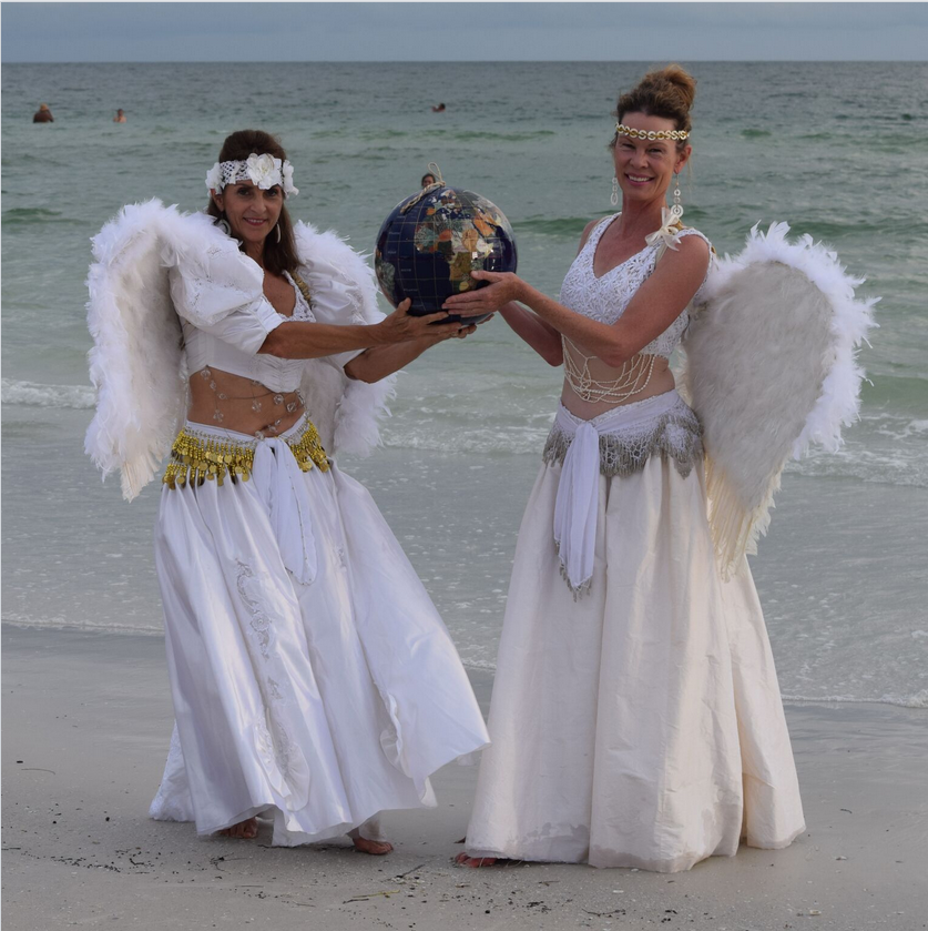 ANGELS ON SIESTA KEY? Jeannie Bloomfield of Venice and Ann Raabe of Boulder, CO holding the globe above the amazing Siesta Beach shoreline. They came to the Key to dance at the drum circle.  The two previously danced at